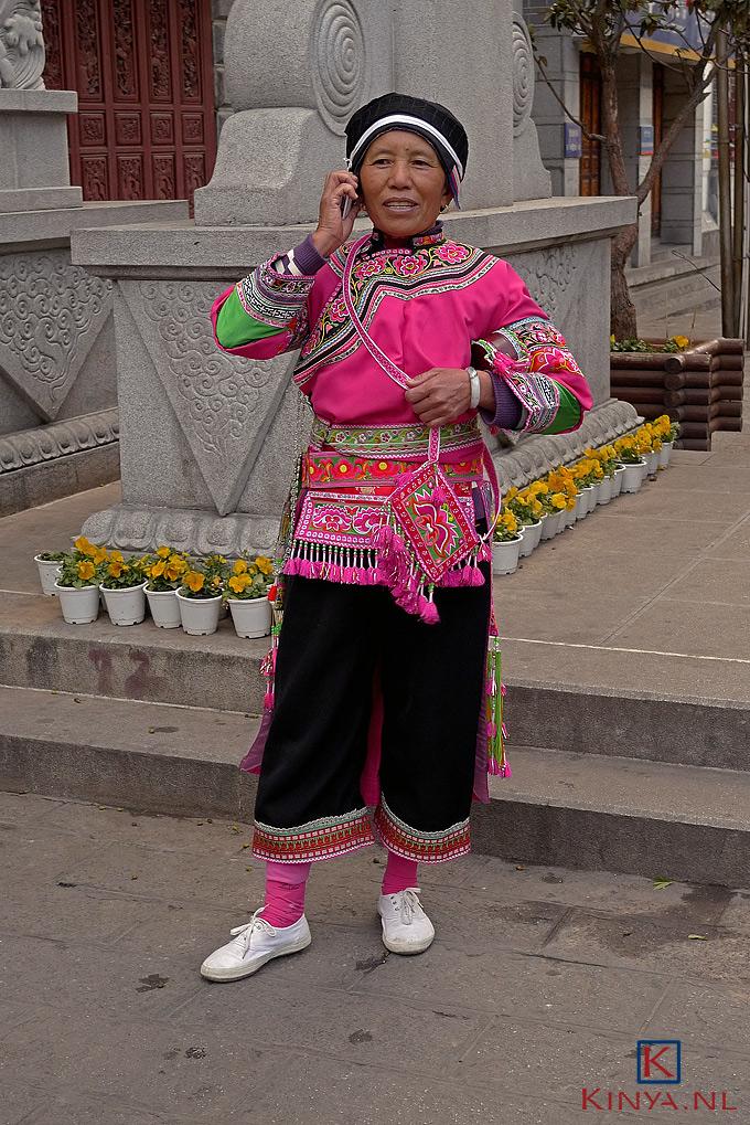 Bellende Chinese Bai-vrouw nog in traditionele rijk geborduurde dracht